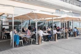 אנשים אוכלים באזור מוצל במסעדת הזקן והים