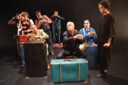 מיצג במרכז נא לגעת - אנשים יושבים על מזוודות מחזיקים כוסות קפה