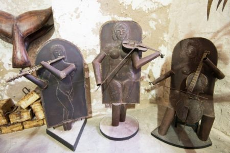 שלושה פסלי מתכת: תזמורת של נגנים עומדים על שולחן