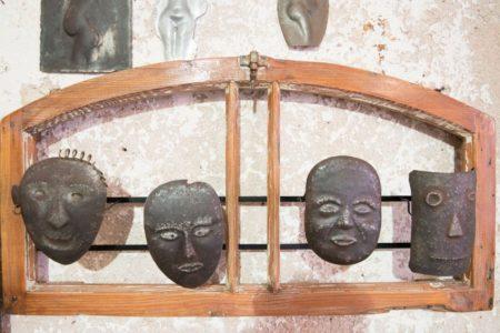 עבודת אמנות של האמן מוטי נטף. ארבעה פסלי פנים ממתכת על פני מסגרת עץ