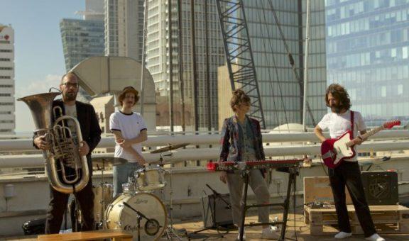 להקת בום בם, ארבעה נגנים על גג בניין עם כלי נגינה וברקע גורדי שחקים