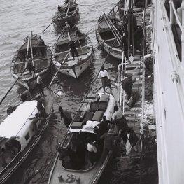 """עולים חדשים יורדים מאוניית נוסעים אל סירות מנוע, בדרכם לנמל יפו. 1933. צילום: זולטן קלוגר, לע""""מ."""